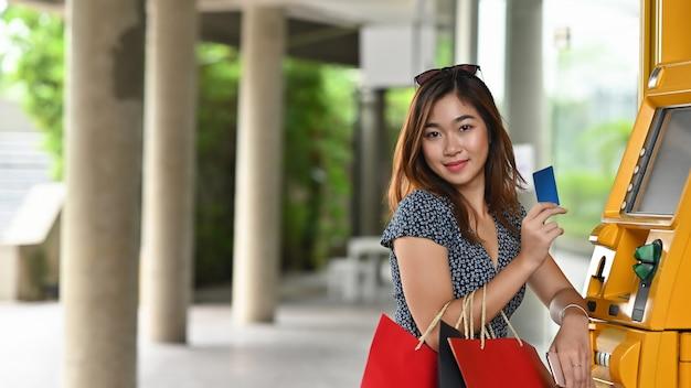 若いショッピング少女とショッピングモールでクレジットカードとatmを保持しているショッピングバッグ。