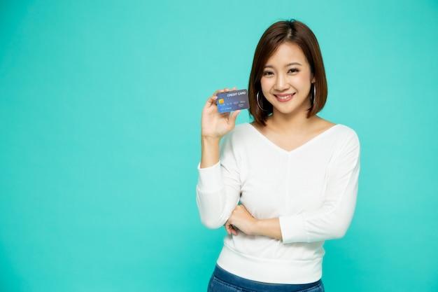 Atmまたはデビットまたはクレジットカードを保持し、緑の壁、アジアの女性モデルに分離された多くのお金を費やしてオンラインショッピングに使用して幸せな若い女の肖像