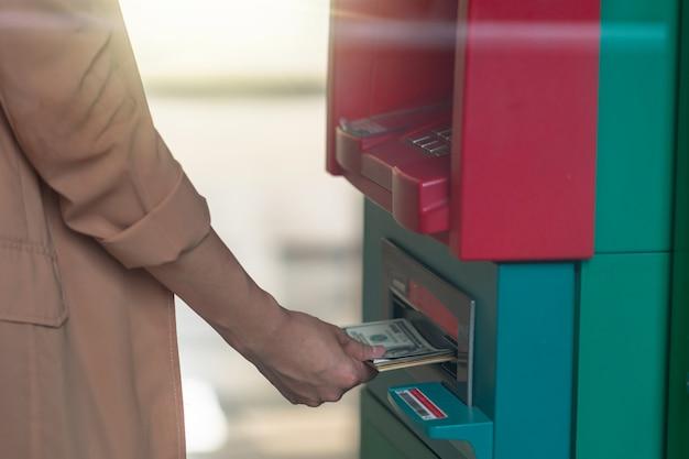 クローズアップの女の子が財布を持って、atmで現金を引き出す