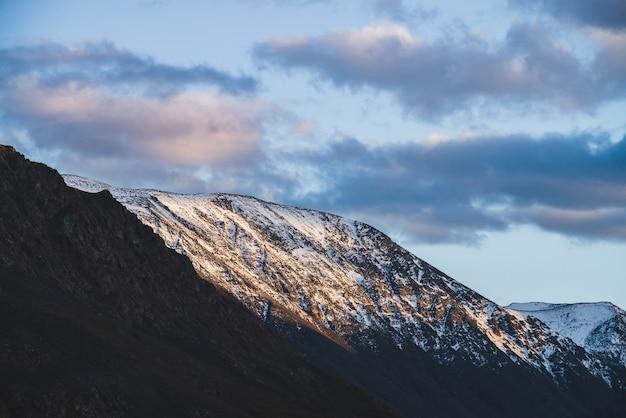 Атмосферный альпийский пейзаж на заснеженный горный хребет на закате. снег сияет золотым светом на вершине горы. красивый блестящий снежный верх. вечернее пасмурное небо. прекрасные пейзажи в золотых оттенках заката.