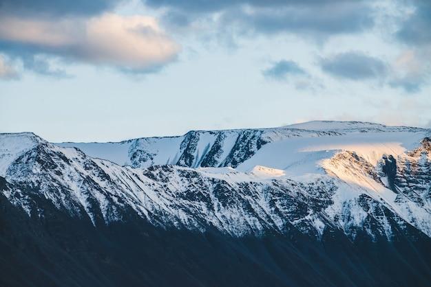 Атмосферный альпийский пейзаж на заснеженный горный хребет на закате.