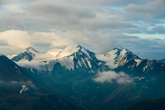 Атмосферный альпийский пейзаж с большими снежными горами среди низких облаков и высокогорной долиной с ручьем талой воды в золотой час. замечательные пейзажи массивного ледника на гигантском горном хребте на рассвете