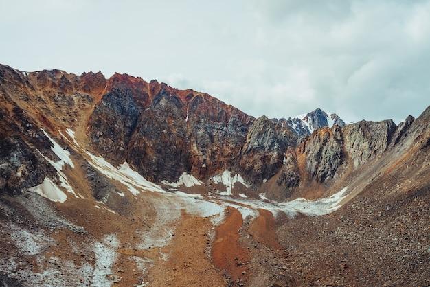 거대한 바위와 돌로 덮인 특이한 빙하 혀가있는 분위기있는 고산 풍경. 아름다운 뾰족한 바위 산 벽. 빙하 혀가있는 멋진 생생한 고원 풍경. 어스 톤.