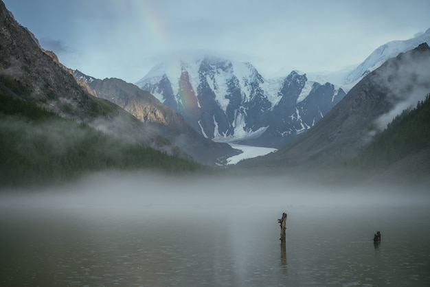 Atmospheric alpine landscape with mountain lake in fog and snowy mountains with rainbow in rainy weather. gloomy scenery with mountain lake with rainy circles in fog on water and low clouds in valley.