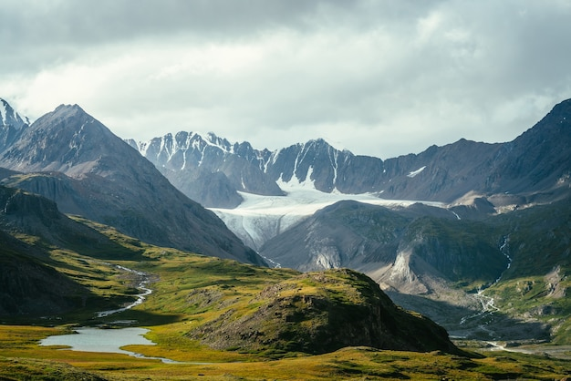 Atmospheric alpine landscape with mountain lake in green valley and glacier under cloudy sky. awesome highland scenery with beautiful glacial lake among sunlit hills and rocks against mountain range.