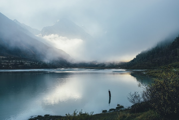 Atmospheric alpine landscape with mountain lake and high snow-covered mountain in dense low clouds. beautiful low lighting scenery with pointy peak in thick fog and golden sunshine reflection in lake.