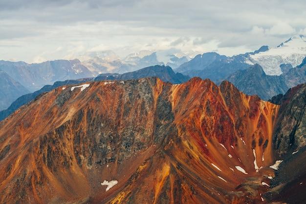 Атмосферный альпийский пейзаж с красными скалами в золотой час.