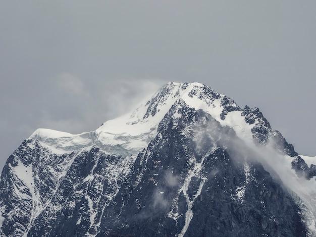 雪の灰色の空の下に雪に覆われた山の頂上と大気の高山の風景。雪のある美しい先のとがった山と低い雲のある高い雪の山の壁の素晴らしい景色。