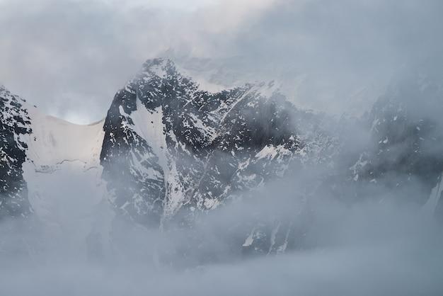 낮은 구름 안에 눈 덮인 산들이있는 분위기있는 고산 풍경. 흐린 하늘에 아름 다운 빙하입니다. 구름을 통해 아침 빛. 파스텔 톤의 짙은 안개 속에서 록키가있는 아름다운 미니멀리스트 풍경.