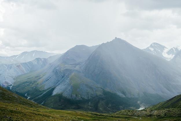 우울한 흐린 하늘 아래 날카로운 절정과 함께 패스에서 큰 산까지의 대기 고산 전망.