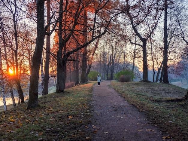 公園の曲がりくねった道で日の出と女性のシルエットと雰囲気のある秋の朝の風景。