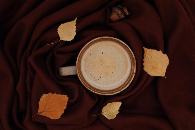 暖かい色の大気の秋または秋の朝のコーヒーは黄色の葉どんぐり黒の熱いカップを残します...