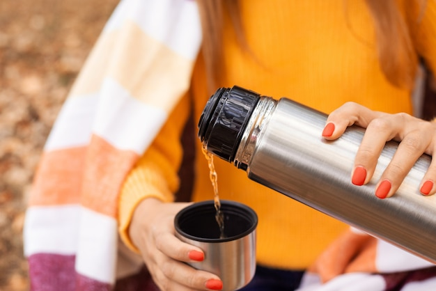 Атмосферное осеннее фото женщины, наливающей горячий чай в чашку