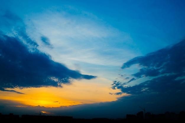 都市の建物のシルエットの背後にある大気の青い曇り空。濃い雲とコピースペースのための明るい黄色の日当たりの良い光と日の出のコバルトとオレンジ色の背景。雲の上のシアンの天国。