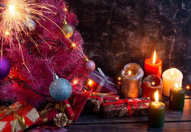 Атмосферная новогодняя или новогодняя композиция розовая елка на черном фоне свечи подарки ...