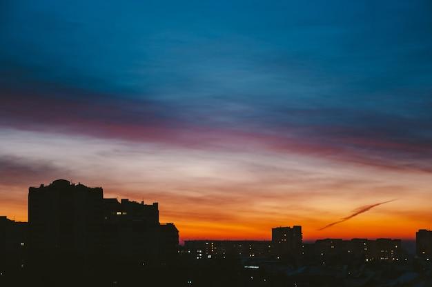 Атмосферные облака в городе на закате