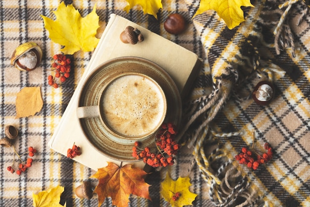 Atmospheric cozy autumn composition hot mug of coffee book fall leaves chestnut ashberry acorns and ...