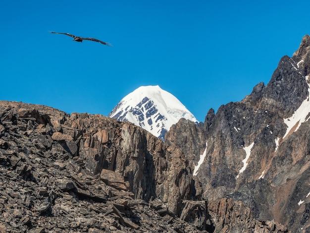 高い雪に覆われた山と空を飛ぶ凧のある澄んだ青い空のある雰囲気のある風景。