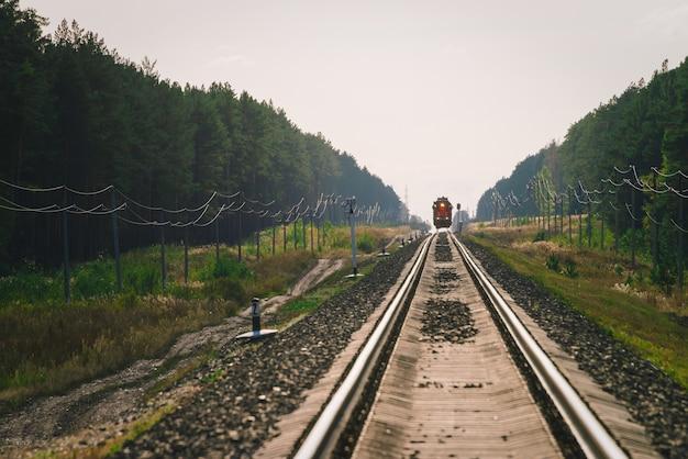 地平線に機関車があり、鉄道に蜃気楼がある大気の風景