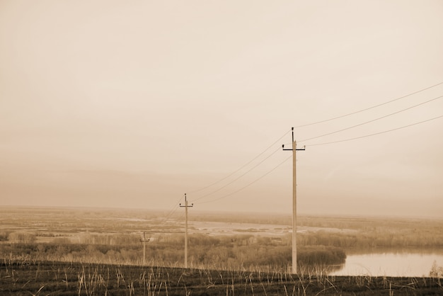 Atmospheric landscape with power lines in field on background of river under sepia sky.