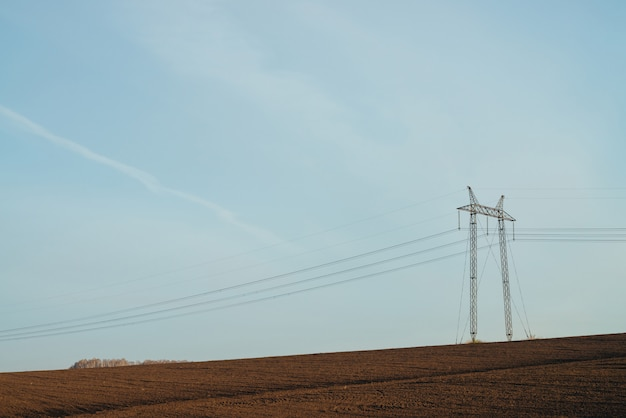 Atmospheric landscape with power lines in field under blue sky.
