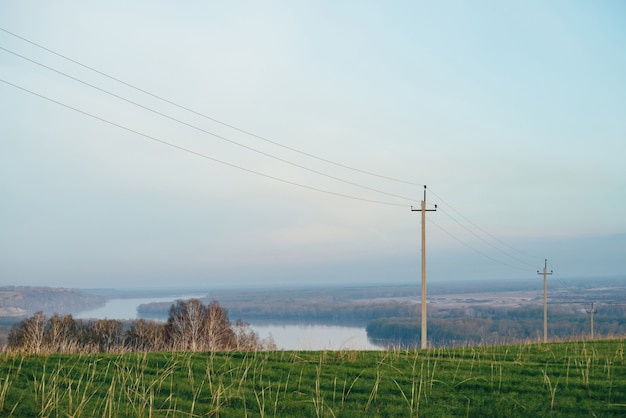 Atmospheric landscape with power lines in green field on background of river under blue sky.