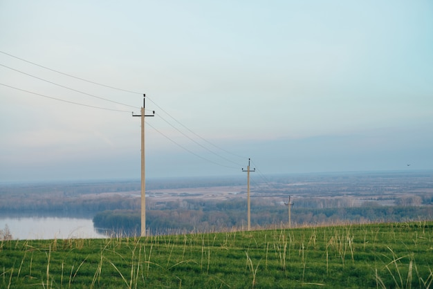 Atmospheric landscape with power lines in green field on background of river under blue sky