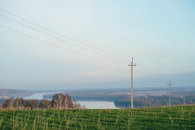 Атмосферный пейзаж с линиями электропередач в зеленом поле на фоне реки под голубым небом.