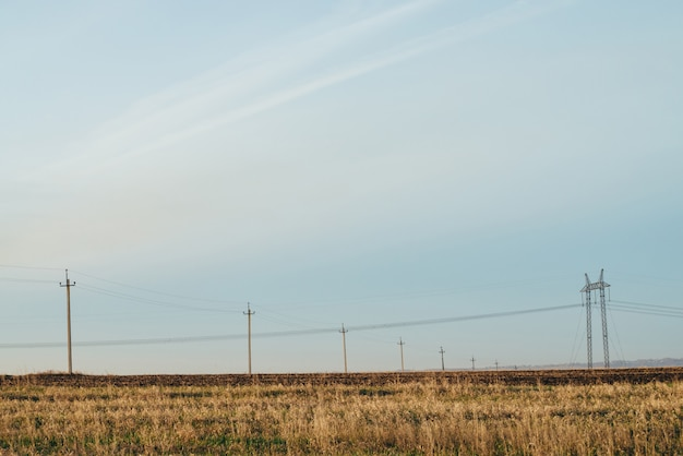 Atmospheric landscape with power lines in yellow field under blue sky.
