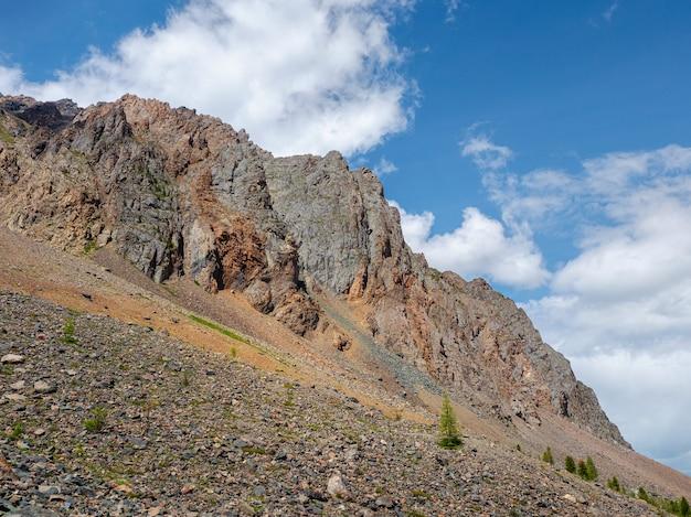 日当たりの良い光の中で先のとがった頂上と岩山の壁のある雰囲気のある風景。手前の緩い石の山の斜面。鋭い石の山。
