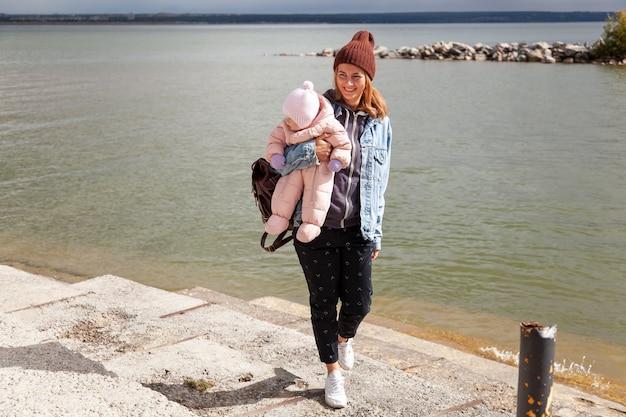 Атмосферная фотография образа жизни женщины в джинсовой куртке гуляет и играет со своей маленькой дочерью на фоне моря в солнечный день.