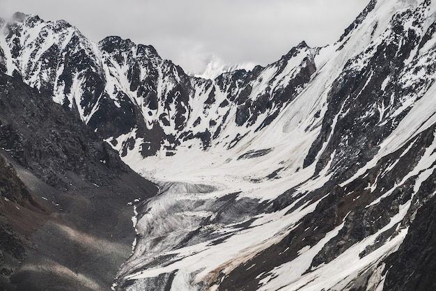 Atmospheric minimalist alpine landscape of big snowy mountain with massive glacier. cloudy sky over great rocky mountains. glacier tongue near snowbound mountainside. majestic scenery on high altitude