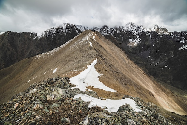 Atmospheric minimalist alpine landscape to massive snowy mountain range. firn or snow on combe rocky hill. cloud sky over big snowbound ridge. rock of boulder stream. majestic scenery on high altitude