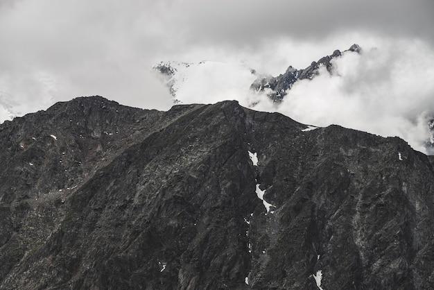 大きなロッキー山脈の壁と低い雲の雪に覆われたピークを持つ大気のミニマリストの高山の風景