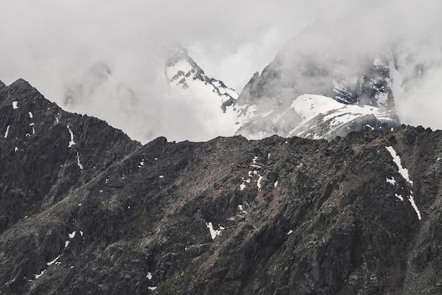 Атмосферный минималистский альпийский пейзаж с большой скалистой горной стеной и заснеженной вершиной в низких облаках
