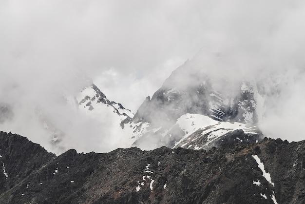 Атмосферный минималистский альпийский пейзаж с большой скалистой горной стеной и заснеженной вершиной в низких облаках.