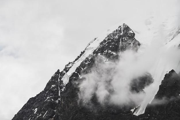 Атмосферный минималистский альпийский пейзаж с висящим ледником на заснеженной скалистой горной вершине