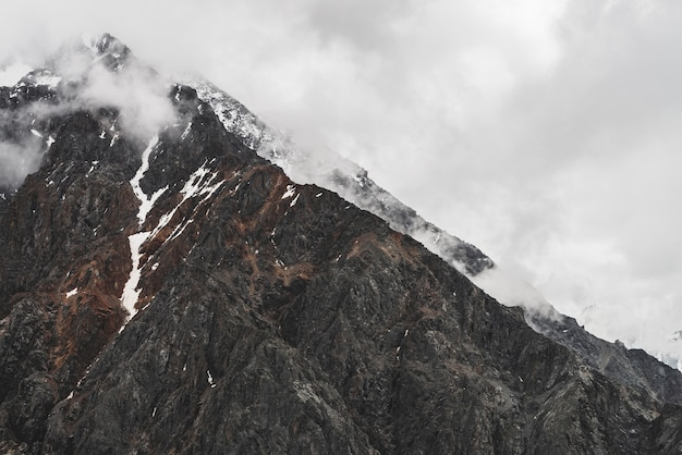 Atmospheric minimalist alpine landscape with hanging glacier on snowy rocky mountain peak. low clouds among snowbound mountains. serac on glacial edge. majestic misty foggy scenery on high altitude.