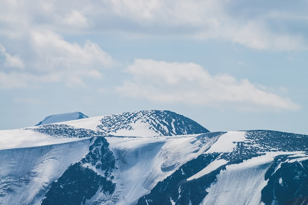 Atmospheric minimalist alpine landscape with massive hanging glacier on snowy mountain peak. big balcony serac on glacial edge. cloudy sky over snowbound mountains. majestic scenery on high altitude.