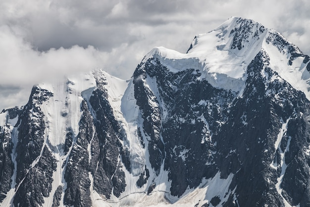 Atmospheric minimalist alpine landscape with massive hanging glacier on snowy mountain peak