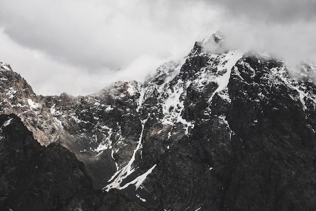 Атмосферный минималистский альпийский пейзаж со снежной скалистой горной вершиной