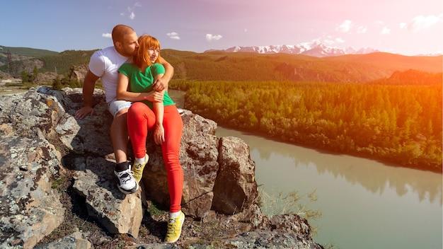 Атмосферный момент для влюбленных в горах. пешие прогулки женщина и мужчина сидят на вершине холма и смотрят на красивый пейзаж. путешествия, образ жизни и концепция выживания, вид сзади