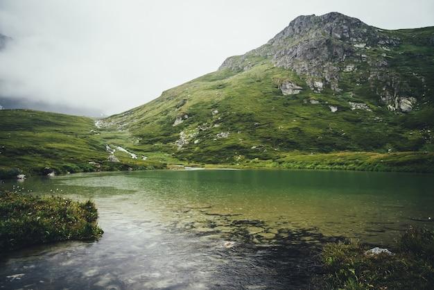 澄んだ湖の水に雨の輪がある雰囲気のある山の風景。石のある山の湖の砂底。雨天時の透明な水面に雨の輪が広がる美しい風景。