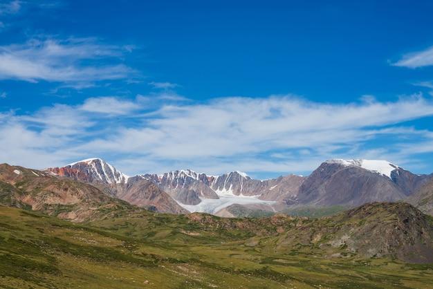 青い曇り空の下に大きな美しい氷河と鋭い岩がある大気の山の風景。大きな氷舌のある風光明媚な高山の風景。緑の峠から茶色の岩までの素晴らしい景色。