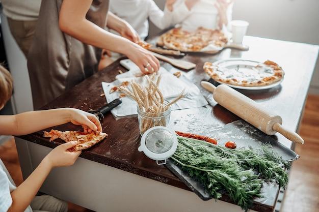 Атмосферный портрет счастливой семьи на современной кухне. мать готовит пиццу, а ее дети пробуют и едят, сидя за столом.