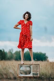 赤いドレスを着た若い女性の大気の肖像画は古いレトロなテレビの上に立つ
