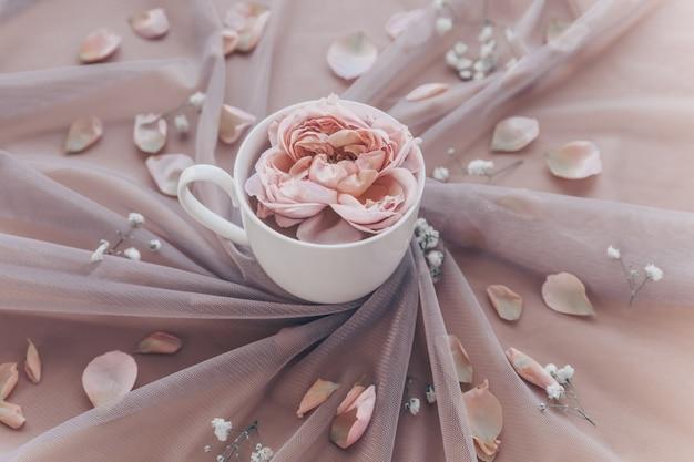 Атмосферная романтическая композиция с тюлем и розовой розой в чашке.