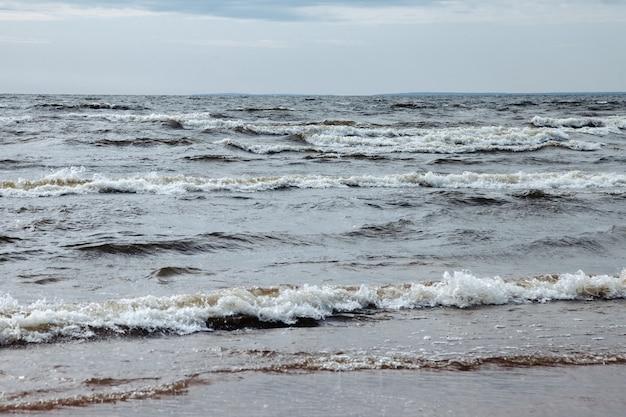 Атмосферный пейзаж драматическое балтийское море, волны и брызги воды на волнорезах. природа северный cloudscape на побережье океана. окружающая среда с переменчивой погодой, изменением климата. бурные абстрактные фоны