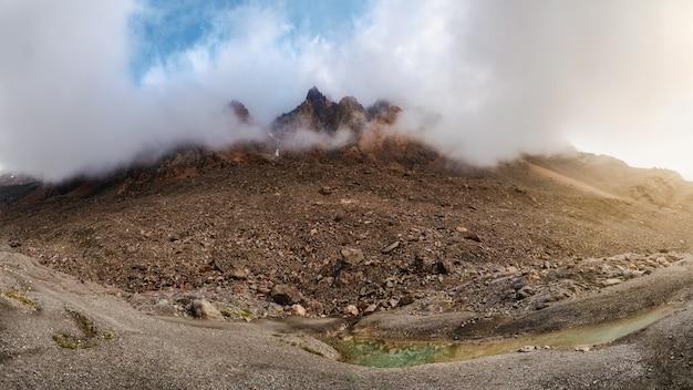 大気の晴れた朝の山の風景。高地のパノラマ風景。岩の鋭い山頂が雲と朝の霧から見えます。
