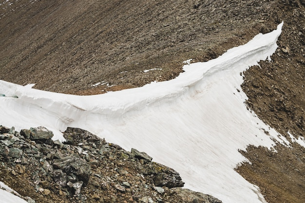 大気の織り目加工のミニマルな高山の風景。大きなくし状の岩が多い山の尾根に雪が降っている。積雪の丘。岩の岩。高地の雄大な景色。